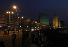File: People stand along Marine Drive, after tight security arrangements put in place for U.S. President Barack Obama's visit were eased, in Mumbai November 7, 2010.