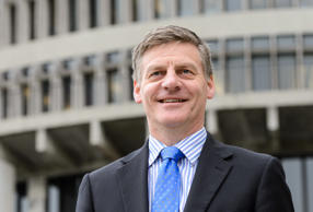 Bill English, New Zealand's deputy prime minister and finance minister, poses for a photograph outside the New Zealand Parliament Building complex in Wellington.