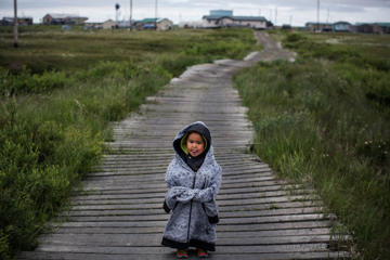 A Yupik child stands on raised, wooden sidewalks, used to help cross unstable ground, on June 30, 2015 in Newtok, Alaska.