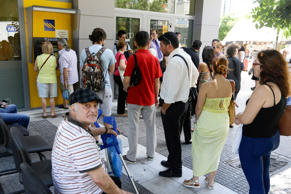 People stand in a queue to use ATM of a bank as others sit on chairs put out from the branch in Athens, Tuesday, July 7, 2015. Greek Prime Minister Alexis Tsipras was heading Tuesday to Brussels for an emergency meeting of eurozone leaders, where he will try to use a resounding referendum victory to eke out concessions from European creditors over a bailout for the crisis-ridden country.