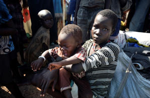 In this photo taken June 29, a newly-arrived displaced woman holds a child as they sit in the UN base in Bentiu, South Sudan.