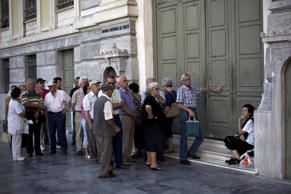 Pensioners wait in front of the gate of the National Bank of Greece as they wait to withdraw money, with a maximum of 120 euros, in Athens July 7, 2015. Eurozone leaders will hold an emergency summit in Brussels on July 7 to discuss the fallout from Greek voters' defiant 'No' to further austerity measures, with the country's Prime Minister Alexis Tsipras set to unveil new proposals for talks.