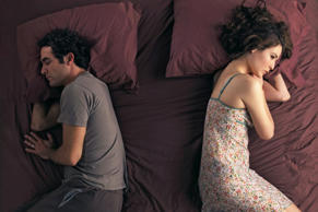 Unhappy couple sleeping in bed