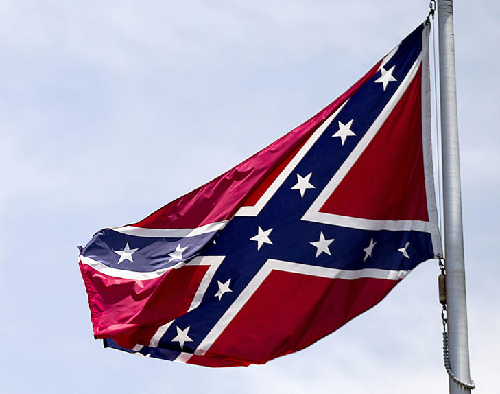 In this June 30, 2015 file photo, a Confederate flag flies at the base of Stone Mountain in Stone Mountain, Ga. Mainstream country music has been quietly distancing itself from the Confederate flag for years, but as the debate reignites following a massacre at a black church in South Carolina on June 17, country artists still struggle to articulate their feelings about the flag's history and symbolism.