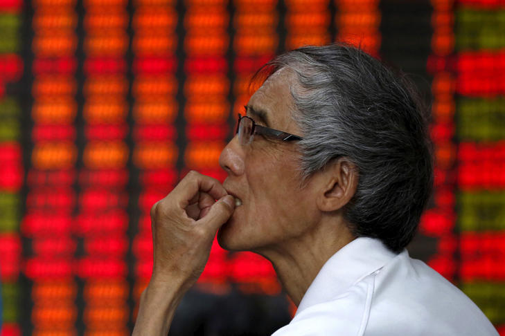 An investor watches an electronic stock market display in Shanghai, China, July 10, 2015.