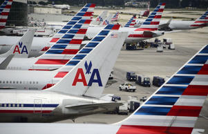 American Airlines passenger planes are lined up on the tarmac at Miami International Airport.