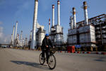 In this Monday, Dec. 22, 2014 photo, an Iranian oil worker rides his bicycle at the Tehran's oil refinery south of the capital Tehran, Iran.