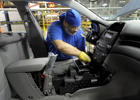 A General Motors Auto worker installs a dashboard component into a 2015 Chevrolet Malibu being built at GM's Fairfax assembly plant in Kansas City, Kansas May 4, 2015.