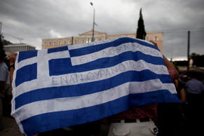 "File: Protestors shelter from rain under a Greek national flag that reads ""Greeks need only a sky full of stars"" during a demonstration in support of the European Union (EU) in Athens, Greece, on Tuesday, June 30, 2015."