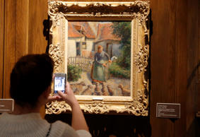 "A visitor to the Fred Jones Jr. Museum of Art at the University of Oklahoma in Norman, Okla., takes a photograph of a piece called ""Shepherdess Bringing in Sheep"" by French impressionist artist Camille Pissarro, in February 2014 at the museum."