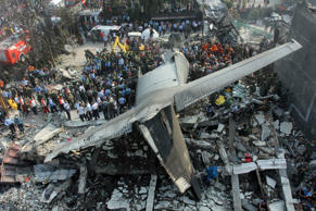 Rescuers search for victims at the site where an air force cargo plane crashed in Medan, North Sumatra, Indonesia, on Tuesday.