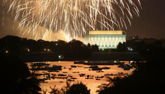 People watch from boats on the Potomac River as Independence Day fireworks light the sky over Washington DC.