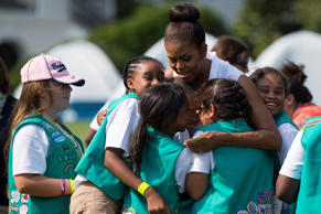 First lady Michelle Obama hugs a group of Girl Scouts during a Lets Move! event on the South Lawn of the White House, on Tuesday, June 30, 2015, in Washington.