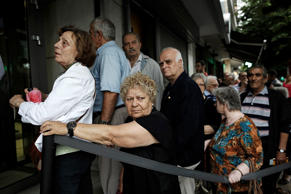 Pensioners queue to get access inside an open Piraeus Bank SA bank branch as they attempt to collect their pensions in Thessaloniki, Greece, on Wednesday, July 1, 2015. Even those payments risked putting more pressure on banks than they could bear, underscoring the desperate choices facing the six-month-old left-wing government and voters in the referendum.