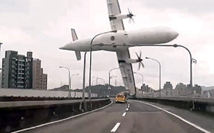 TVBS screen grab taken from a video shows a TransAsia ATR 72-600 turboprop plane clipping an elevated motorway and hitting a taxi before crashing into the Keelung river outside Taiwan's capital Taipei in New Taipei City.