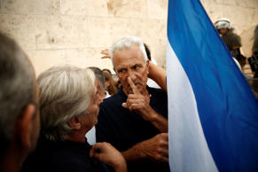A demonstrator gestures to a man as he holds Greek flag during a rally organized by supporters of the YES vote to the upcoming referendum in Athens, Tuesday, June 30, 2015. Greece is set to become the first developed nation to not pay its debts to the International Monetary Fund on time, as the country sinks deeper into a financial emergency that has forced it put a nationwide lockdown on money withdrawals. (AP Photo/Daniel Ochoa de Olza)