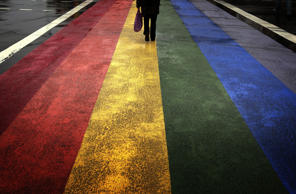 A pedestrian walks across a rainbow pedestrian crossing.