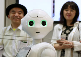 Customers stand in line behind SoftBank Corp.'s humanoid robot Pepper as they wait to pre-order the robot inside the company's store on June 19 in Tokyo.