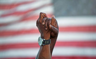 People join hands against the backdrop of an American flag as thousands of marchers meet in the middle of Charleston's main bridge in a show of unity after nine black church parishioners were gunned down during a Bible study, Sunday, June 21, 2015, in Charleston, S.C. David Goldman/AP