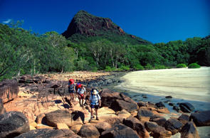 Three hikers on the Thornsborne Trail rock-hopping at Boulder Bay, Hinchinbrook Island National Park, Queensland, Australia.