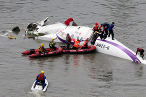 Emergency personnel approach a commercial plane after it crashed in Taipei, Taiwan, Wednesday, Feb. 4, 2015. The Taiwanese commercial flight with 58 people aboard clipped a bridge shortly after takeoff and crashed into a river in the island's capital of Taipei on Wednesday morning.