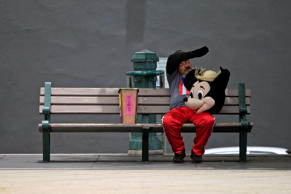 A street performer in a Mickey Mouse costume rests on a bench in Old San Juan, Puerto Rico, Wednesday, July 1, 2015, the day a 11.5% sales tax went into effect, the highest of any U.S. state. The island's administration has been pushing for Congress to let the government and public agencies seek bankruptcy protection, while the White House has said no one is contemplating a federal bailout of Puerto Rico. (AP Photo/Ricardo Arduengo)