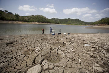 A man and a boy try to fish while standing on the dry shores of the almost empty La Plata reservoir in Toa Alta, Puerto Rico, June 20, 2015. A drought due to subnormal rainfall in several areas has forced the local government to interrupt water supply on several days of the week in most of the metropolitan area of San Juan, affecting over 400,000 homes and businesses, according to local media.