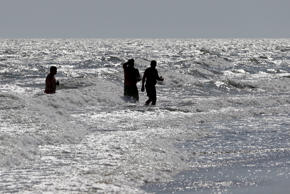 Vacationers walk in the surf in Oak Island, N.C., Monday, June 15, 2015, the day after a 12-year-old girl from Asheboro lost part of her arm and suffered a leg injury, and a 16-year-old boy from Colorado lost his left arm about an hour later and 2 miles away in two separate shark attacks off Oak Island.