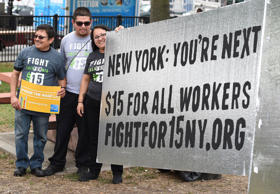New York labor activists stand beside their message sign on June 13, 2015.