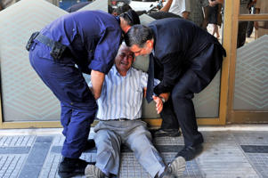 An crying elderly man is assisted  by an employee and a policeman outside a national bank branch as pensioners queue to get their pensions, with a limit of 120 euros, in Thessaloniki on 3 July, 2015. Greece is almost evenly split over a crucial weekend referendum that could decide its financial fate, with a 'Yes' result possibly ahead by a whisker, the latest survey Friday showed. Prime Minister Alexis Tsipras's government is asking Greece's voters to vote 'No' to a technically phrased question asking if they are willing to accept more tough austerity conditions from international creditors in exchange for bailout funds.