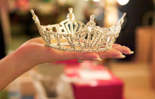 Close up of woman holding tiara. Cheryl Maeder/Getty Images