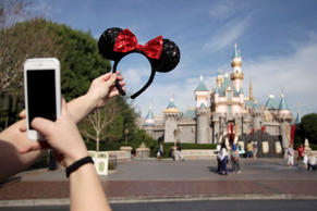 Chelsey Cordero takes pictures of her hairband with the Sleeping Beauty's Castle in the background at Disneyland, Thursday, Jan. 22, 2015, in Anaheim, Calif.