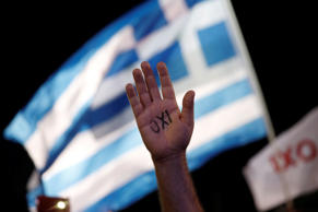 A demonstrator rises his hand reading the word ''No'' as a Greek flag waves during a rally organized by supporters of the No vote in Athens.