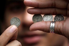 File: A man shows handful of Indian 25 paisa (US $ 0.005) coins prior to deposit at bank for exchange, in Kolkata, India, Wednesday, June 29, 2011.
