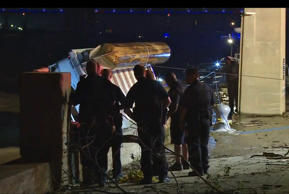 In this image taken from video, police officers look on as an overturned pontoon boat is pulled out of the water of the Ohio River Saturday, July 4, 2015, in Louisville, Ky.