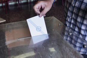 People put referendum votes in the ballot box at a school on July 5, 2015 in Athens, Greece.