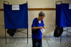 A woman holds her ballot paper before casting it at a polling station in Athens, Sunday, July 5, 2015.