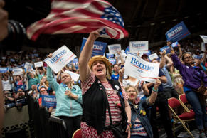 A supporter waves an American flag as others hold signs for Senator Bernie Sanders, an Independent from Vermont and 2016 presidential candidate, during a campaign rally in Madison, Wisconsin, July 1, 2015.