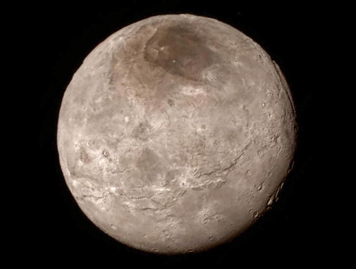 Remarkable new details of Pluto's largest moon Charon are revealed in this image from New Horizons' Long Range Reconnaissance Imager (LORRI), taken late on July 13, 2015 from a distance of 289,000 miles  (466,000 kilometers).  A swath of cliffs and troughs stretches about 600 miles (1,000 kilometers) from left to right, suggesting widespread fracturing of Charon's crust, likely a result of internal processes. At upper right, along the moon's curving edge, is a canyon estimated to be 4 to 6 miles (7 to 9 kilometers) deep.