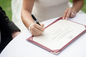 Bride signing wedding certificate