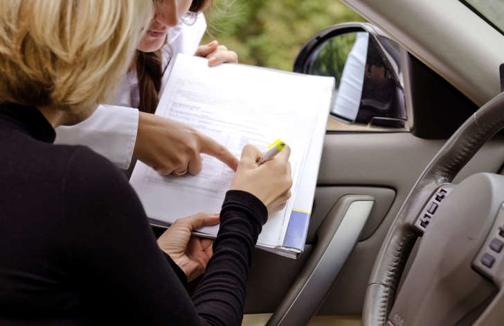 Woman signing a document in car.