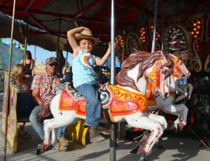 Kingslee Dale tips his hat while riding a merry-go-round at the Bourbon County Fair in Paris.