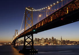 The San Francisco-Oakland Bay Bridge towers over the city skyline at dusk on Wed...