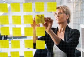 Businesswoman posting post-it