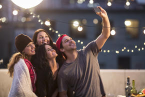 Group of friends taking a selfie at a party. Kevin Kozicki/Getty Images