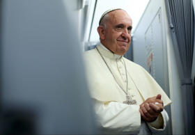 Pope Francis smiles onboard the papal plane during his return to Rome, from Asuncion, Paraguay July 12, 2015.