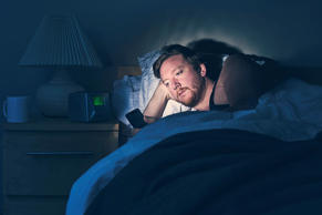 A man uses his smartphone in bed at night.