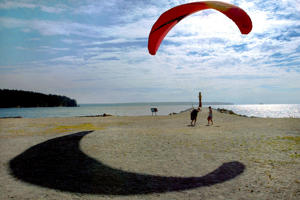 A para-glider casts a long shadow while taking advantage of a good inshore breeze on a beach.
