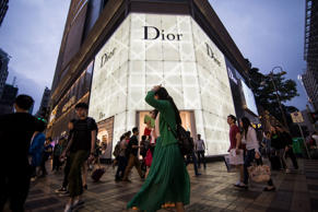 Pedestrians and shoppers walk past a Christian Dior SA store on Canton Road in the Tsim Sha Tsui area of Hong Kong, China, on Saturday, April 18, 2015. Hong Kong is scheduled to release consumer price index (CPI) figures on April 21. Photographer: Billy H.C. Kwok/Bloomberg