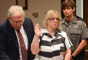 Joyce Mitchell raises her hand during a court appearance with her attorney Stephen Johnston on Tuesday July 28, 2015 in Plattsburgh, N.Y. Mitchell, an instructor in the tailor shop at the Clinton Correctional Facility, pleaded guilty to charges of aiding two inmates convicted of murder by smuggling hacksaw blades and other tools to the pair, who broke out and spent three weeks on the run in June. She faces a sentence of 2 1/2 to 7 years in prison under terms of a plea deal with prosecutors.